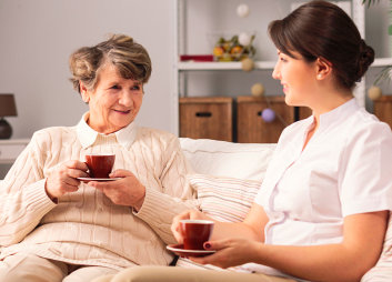 caregiver and old woman having a tea time