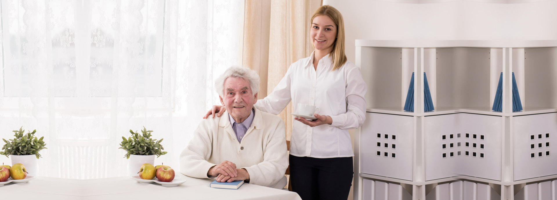 old man showing his genuine smile while the caregiver holding a cup of tea