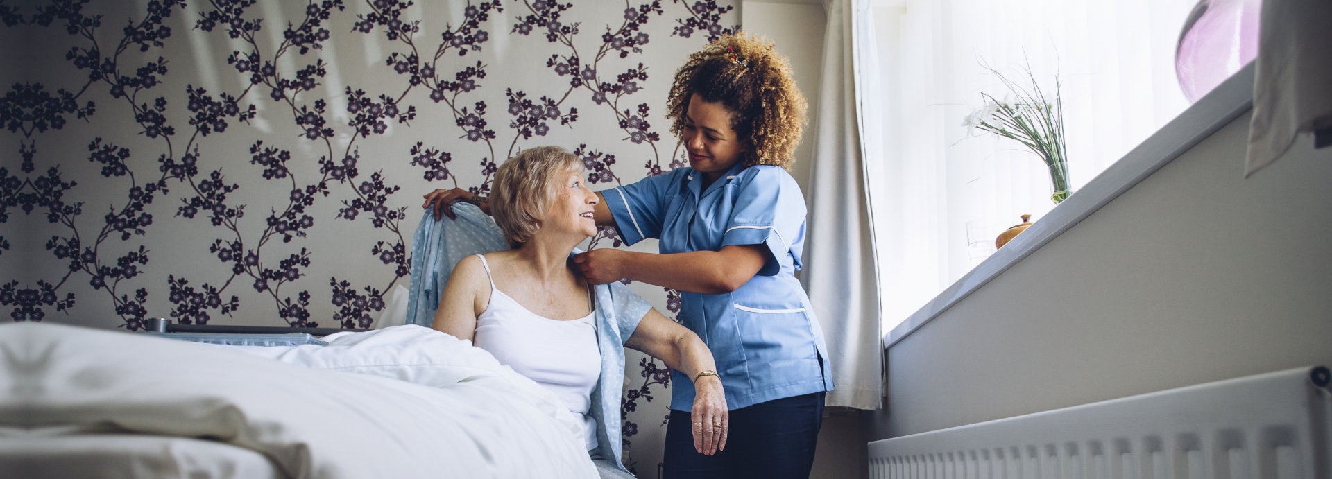 caregiver assisting old woman in dressing