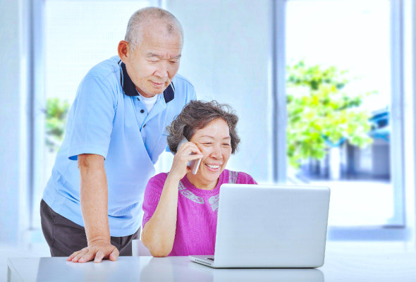 Elderly people using a phone and laptop