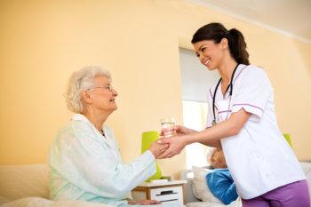 nurse helping senior woman