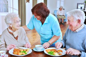 Caregiver serving meal to senior couple