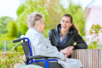 Caregiver laughing while having a talk with an elderly